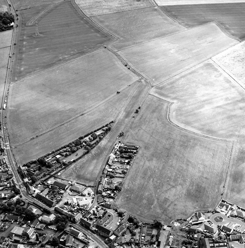 Oblique aerial view centred on the cropmarks of the S end of the Roman Temporary Camp with possible unenclosed settlements and town adjacent, taken from the WNW.