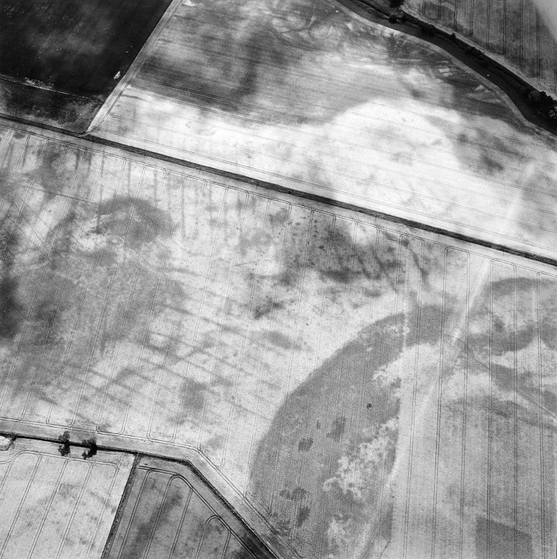 Oblique aerial view centred on the cropmarks of the pit-defined cursus, pits and rig, with pits, rig, ring-ditch and possible quarry adjacent, taken from the N.