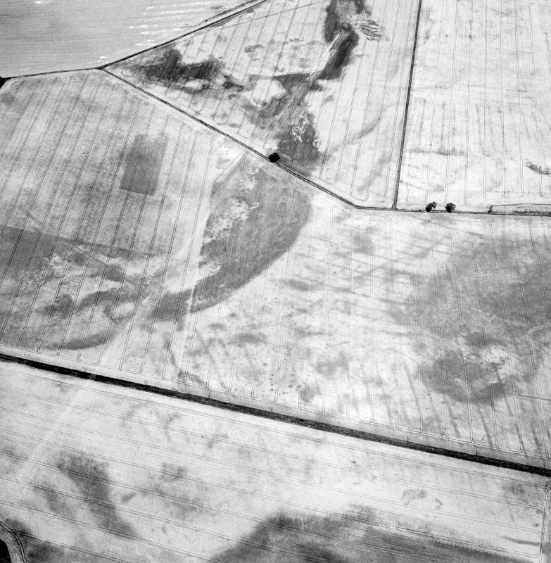 Oblique aerial view centred on the cropmarks of the pit-defined cursus, pits and rig, with pits, rig, ring-ditch and possible quarry adjacent, taken from the SSE.