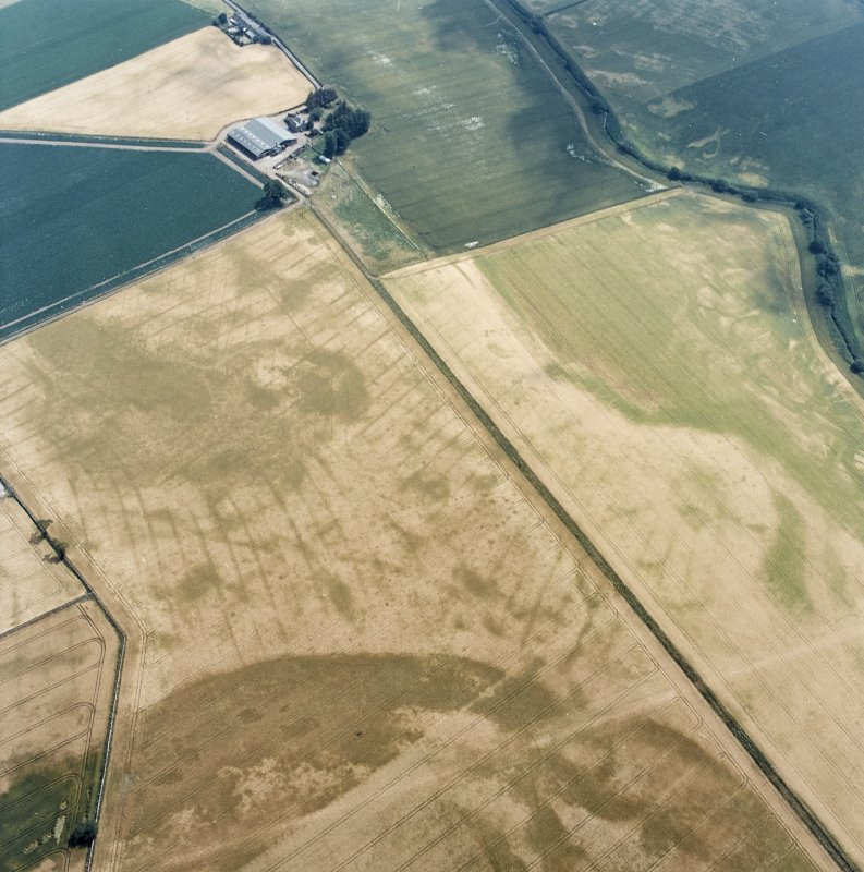 Oblique aerial view centred on the cropmarks of the pit-defined cursus, pits and rig, with farmhouse, pits, rig, ring-ditch and possible quarry adjacent, taken from the WNW.