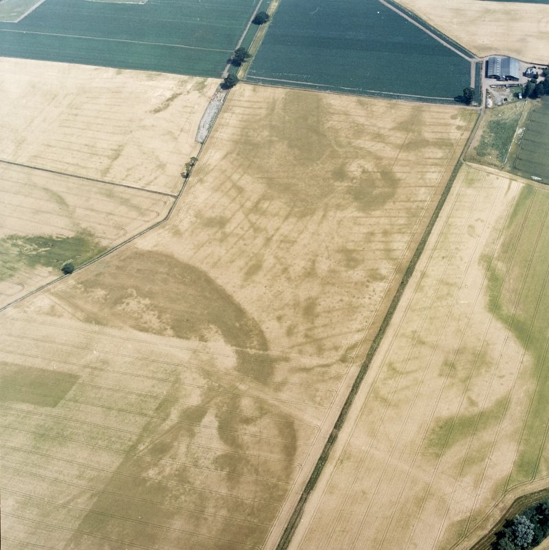 Oblique aerial view centred on the cropmarks of the pit-defined cursus, pits and rig, with farmhouse, pits, rig, ring-ditch and possible quarry adjacent, taken from the WSW.