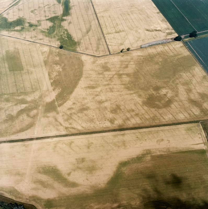 Oblique aerial view centred on the cropmarks of the pit-defined cursus, pits and rig, with pits, rig, ring-ditch and possible quarry adjacent, taken from the S.