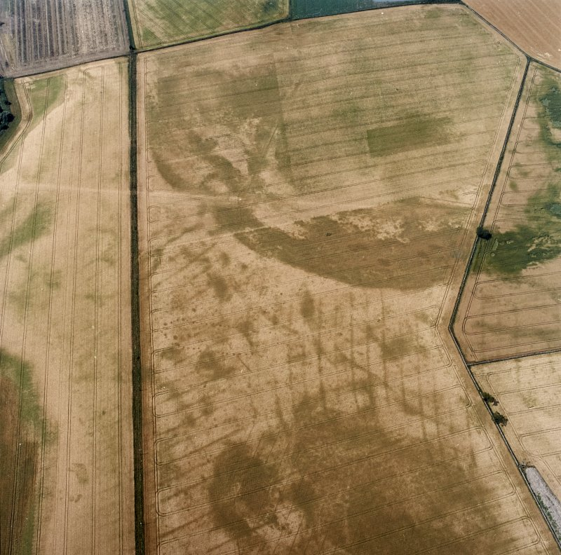 Oblique aerial view centred on the cropmarks of the pit-defined cursus, pits and rig, with pits, rig, ring-ditch and possible quarry adjacent, taken from the E.