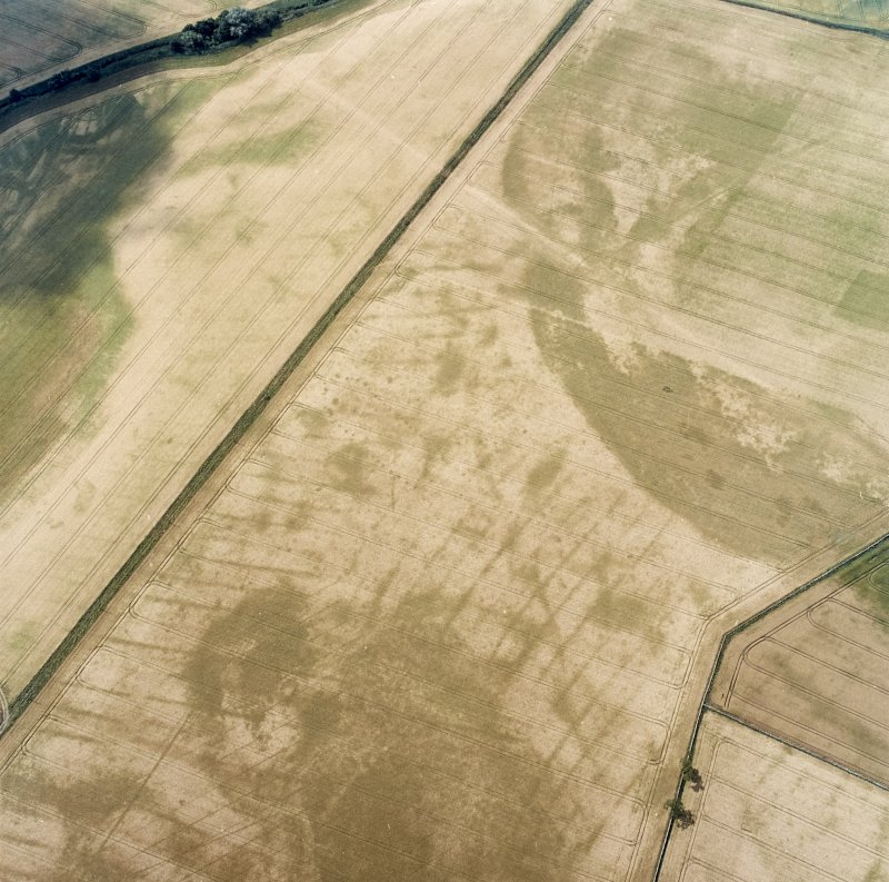 Oblique aerial view centred on the cropmarks of the pit-defined cursus, pits and rig, with pits, rig, ring-ditch and possible quarry adjacent, taken from the ENE.