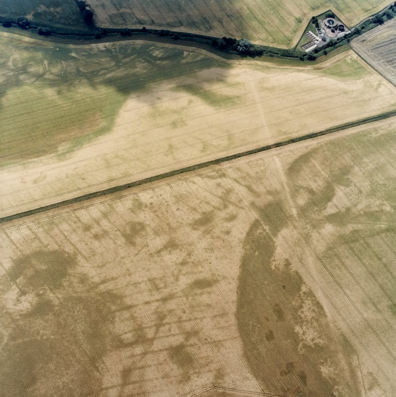 Oblique aerial view centred on the cropmarks of the pit-defined cursus, pits and rig, with pits, rig, ring-ditch and possible quarry adjacent, taken from the NNE.