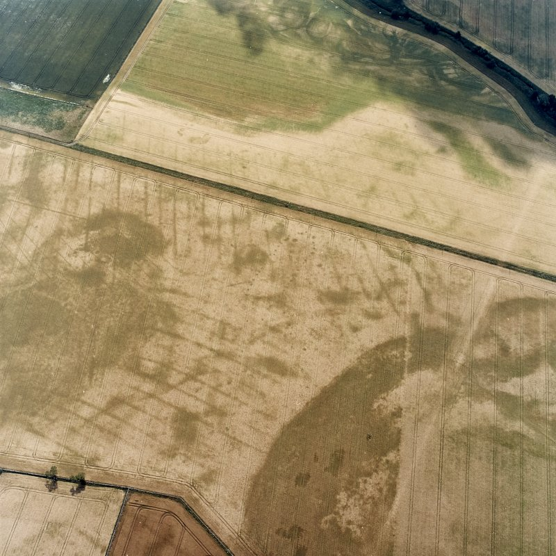 Oblique aerial view centred on the cropmarks of the pit-defined cursus, pits and rig, with pits, rig, ring-ditch and possible quarry adjacent, taken from the NNW.