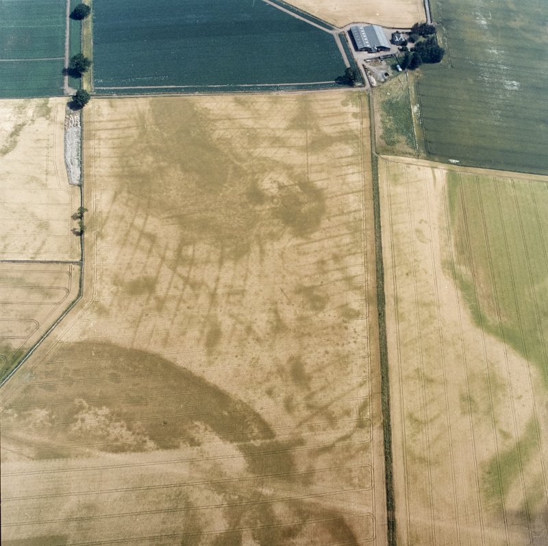 Oblique aerial view centred on the cropmarks of the pit-defined cursus, pits and rig, with farmhouse, pits, rig, ring-ditch and possible quarry adjacent, taken from the W.