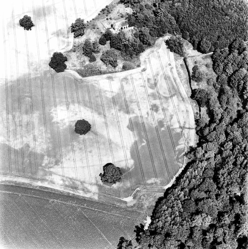 Rossie, oblique aerial view, taken from the S, centred on a series of indeterminate cropmarks and the marks of an enclosure and a trackway. Rossie Church is visible in the top centre of the photograph.