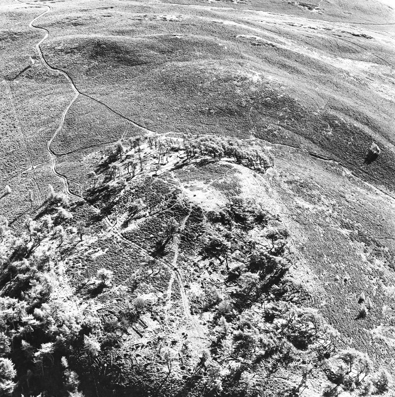 Oblique aerial view centred on the remains of the fort and possible cairn, taken from the NW.