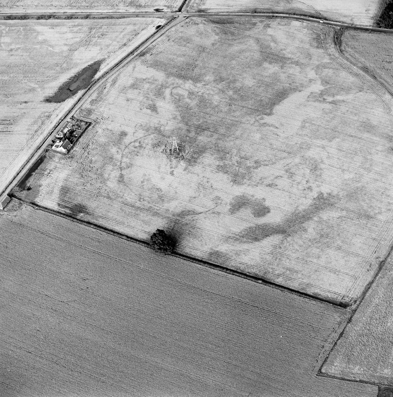Oblique aerial view centred on the cropmarks of an enclosure with possible unenclosed settlement adjacent, taken from the WSW.