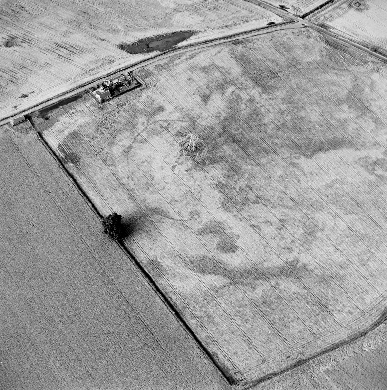 Oblique aerial view centred on the cropmarks of an enclosure with possible unenclosed settlement adjacent, taken from the SSW.