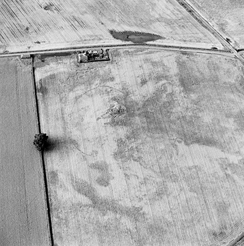 Oblique aerial view centred on the cropmarks of an enclosure with possible unenclosed settlement adjacent, taken from the S.