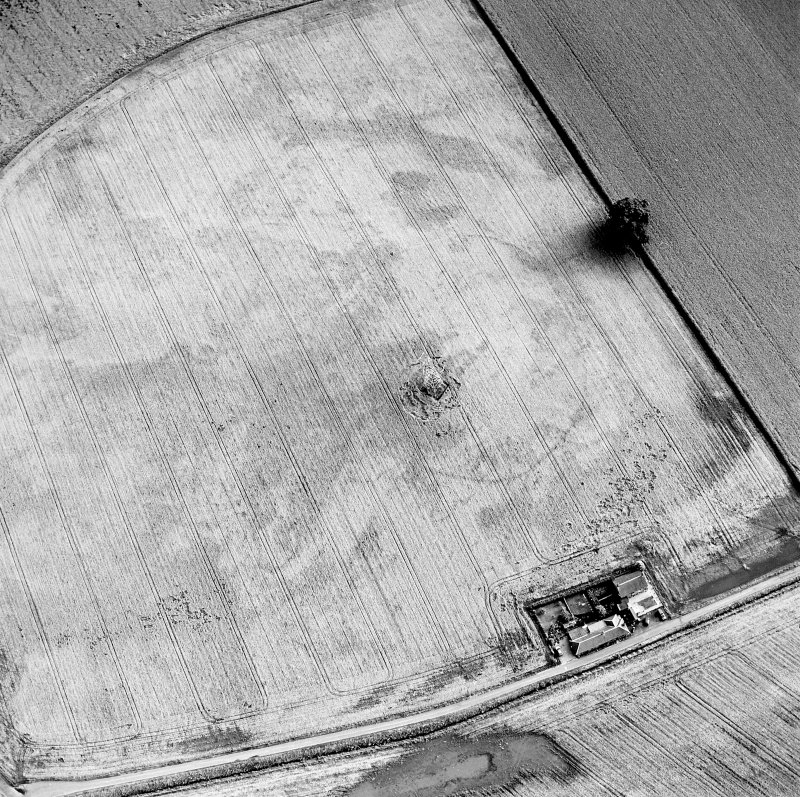 Oblique aerial view centred on the cropmarks of an enclosure with possible unenclosed settlement adjacent, taken from the NNE.