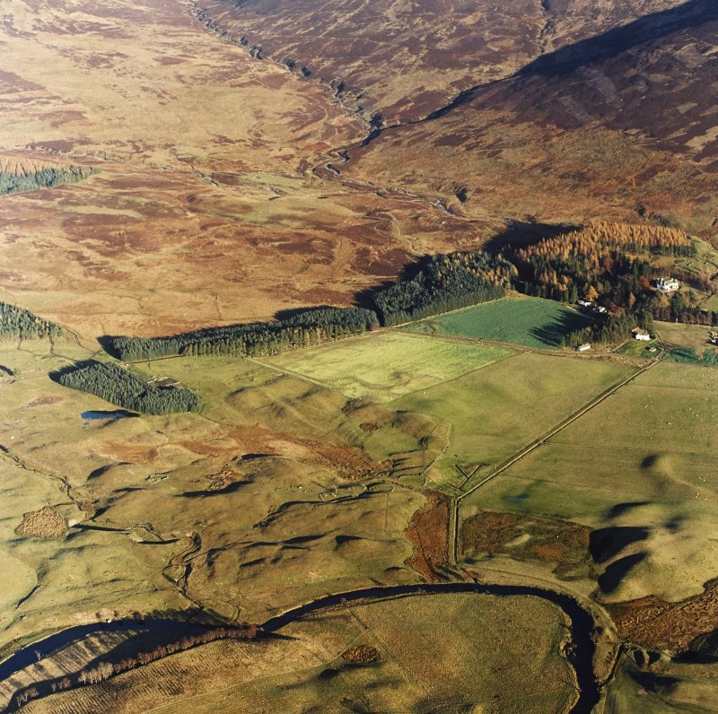 Oblique aerial view centred on the remains of farmsteads, buildings, small carins and rig with hut-circles, small cairns, banks, huts, rig and hunting lodge adjacent, taken from the WSW.