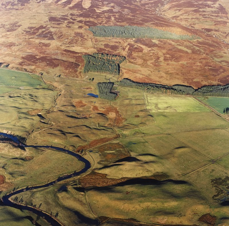 Oblique aerial view centred on the remains of farmsteads, buildings, hut circles, small cairns, banks, huts and rig, taken from the SW.