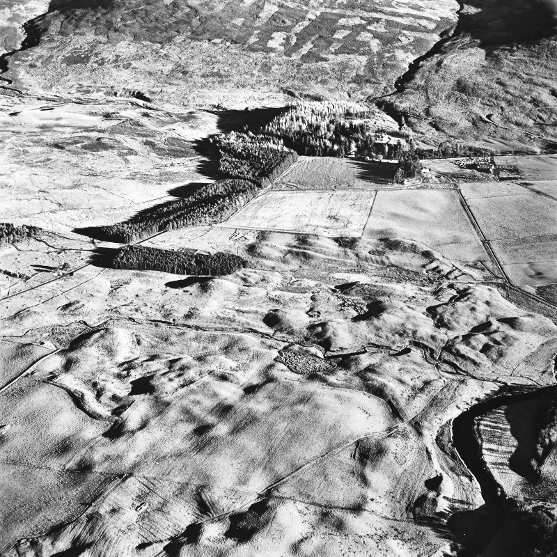 Oblique aerial view centred on the remains of farmsteads, buildings, small carins and rig with hut-circles, small cairns, banks, huts, rig, building and hunting lodge adjacent, taken from the WNW.