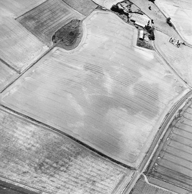 Oblique aerial view centred on the cropmarks of the ring-ditches, unenclosed settlement and barrow with the farmstead adjacent, taken from the NNE.