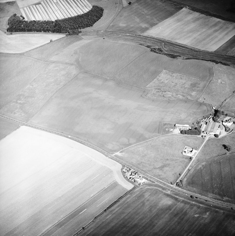 General oblique aerial view centred on the cropmarks of the ring-ditches, unenclosed settlement, enclosures and possible enclosures with the farmhouse and farmsteading adjacent, taken from the W.