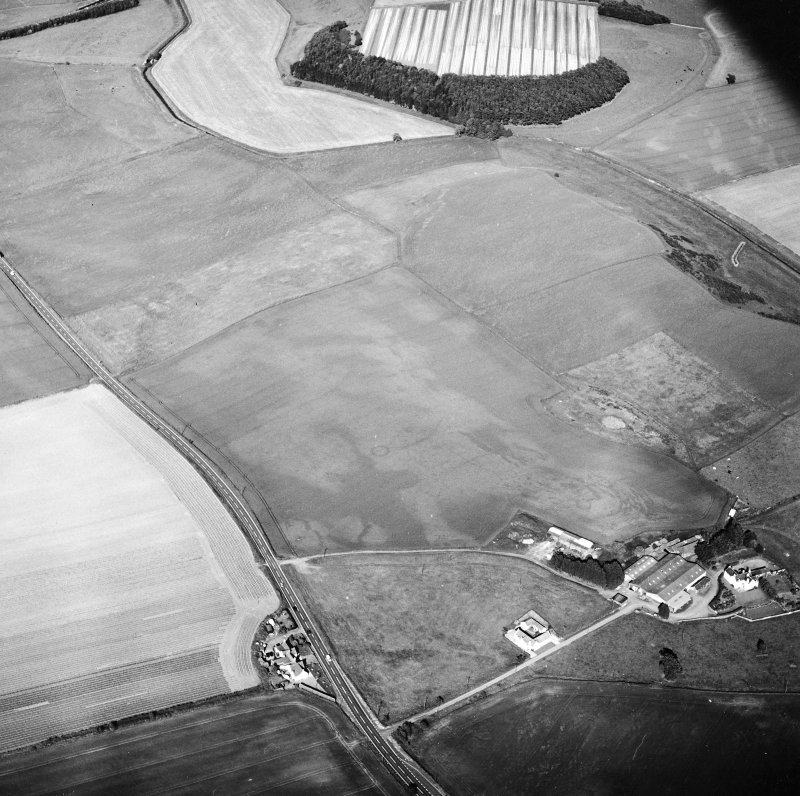 General oblique aerial view centred on the cropmarks of the ring-ditches, unenclosed settlement, enclosures and possible enclosures with the farmhouse and farmsteading adjacent, taken from the WSW.