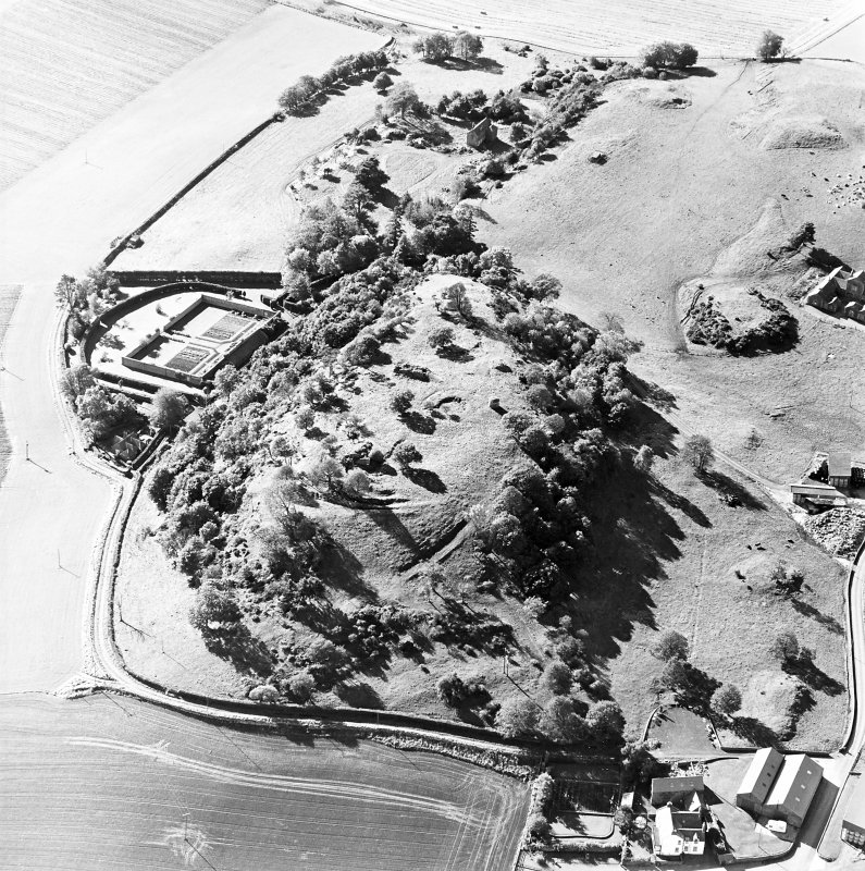 Oblique aerial view centred on the remains of the vitrified fort and broch with the house, walled garden and lodge adjacent, taken from the NE.