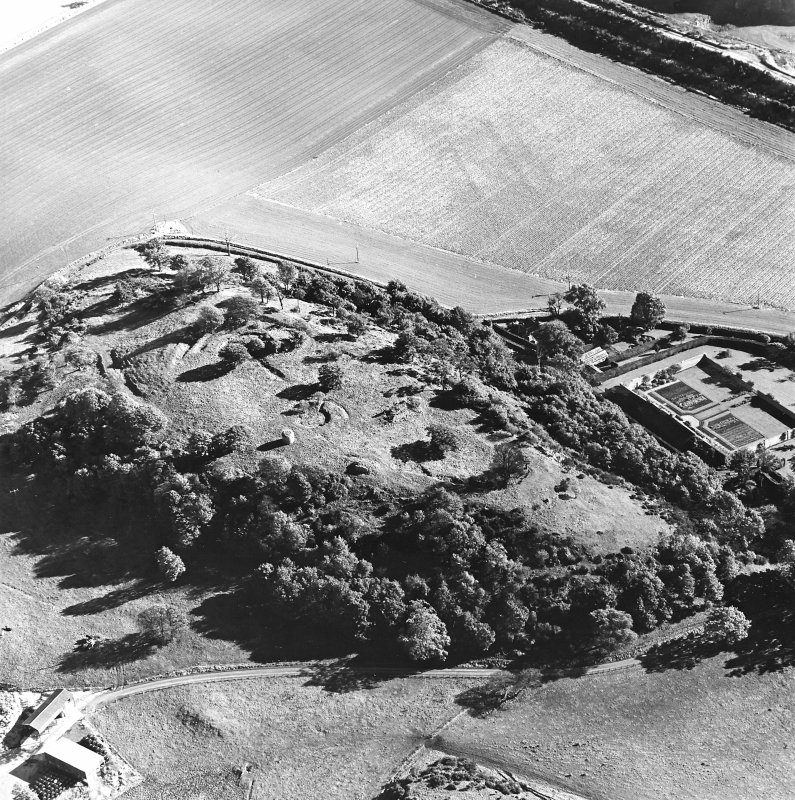 Oblique aerial view centred on the remains of the vitrified fort and broch with the house, walled garden and lodge adjacent, taken from the NW.