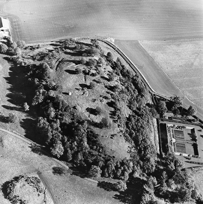 Oblique aerial view centred on the remains of the vitrified fort and broch with the house, walled garden and lodge adjacent, taken from the W.