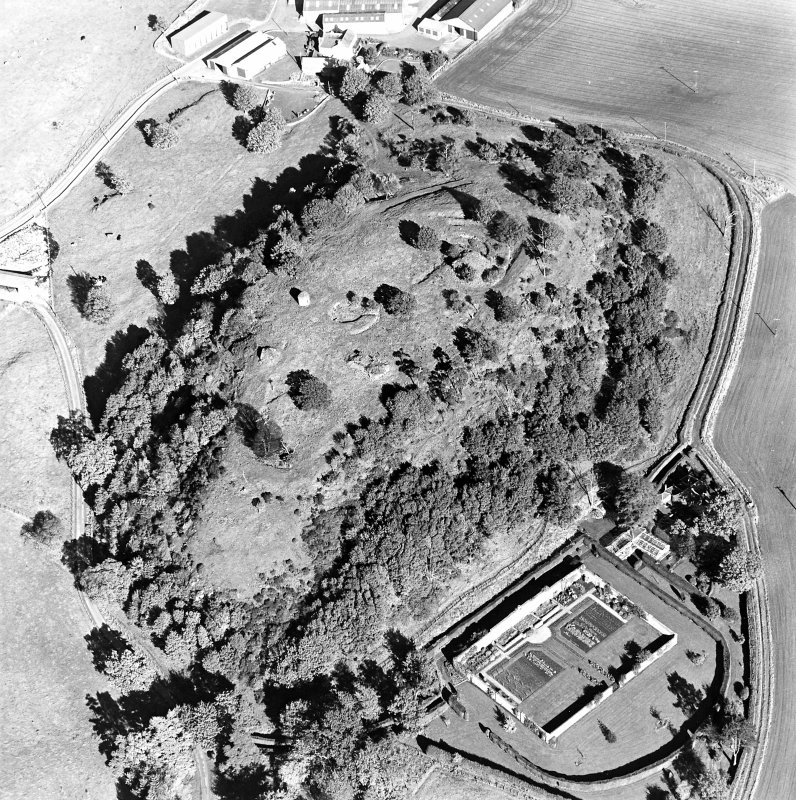 Oblique aerial view centred on the remains of the vitrified fort and broch with the house, walled garden and lodge adjacent, taken from the SW.
