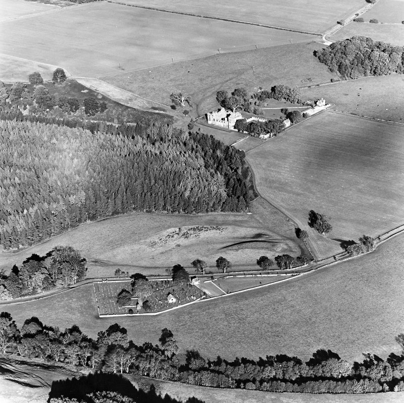 Oblique aerial view of Edzell, Castle Hillock centred on the remains of the Motte-and-bailey castle with castle, church and burial ground adjacent, taken from the SW