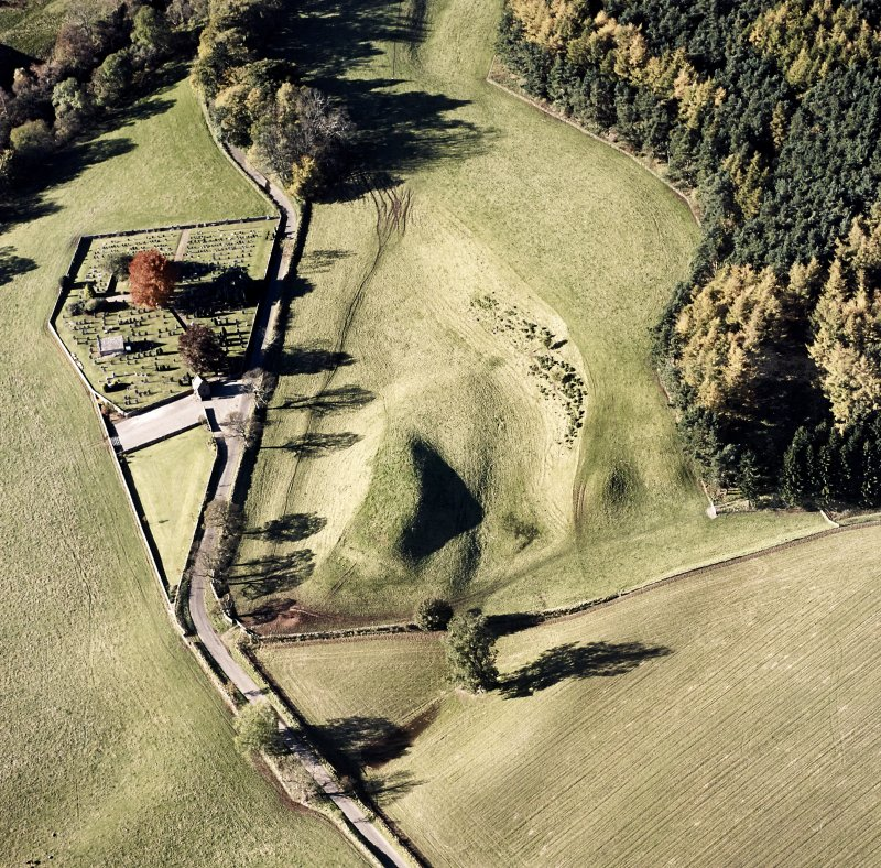 Oblique aerial view of Edzell, Castle Hillock centred on the remains of the motte-and-bailey castle with church and burial ground adjacent, taken from the E.