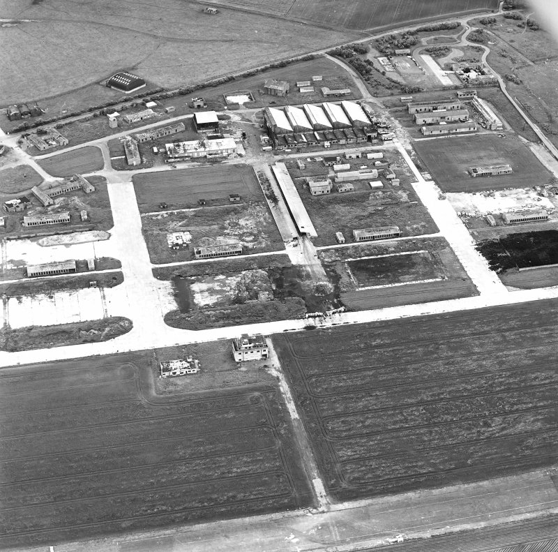 Oblique aerial view of Crail Airfield centred on the remains of the control tower, buildings, huts and aircraft hangars, taken from the ESE.