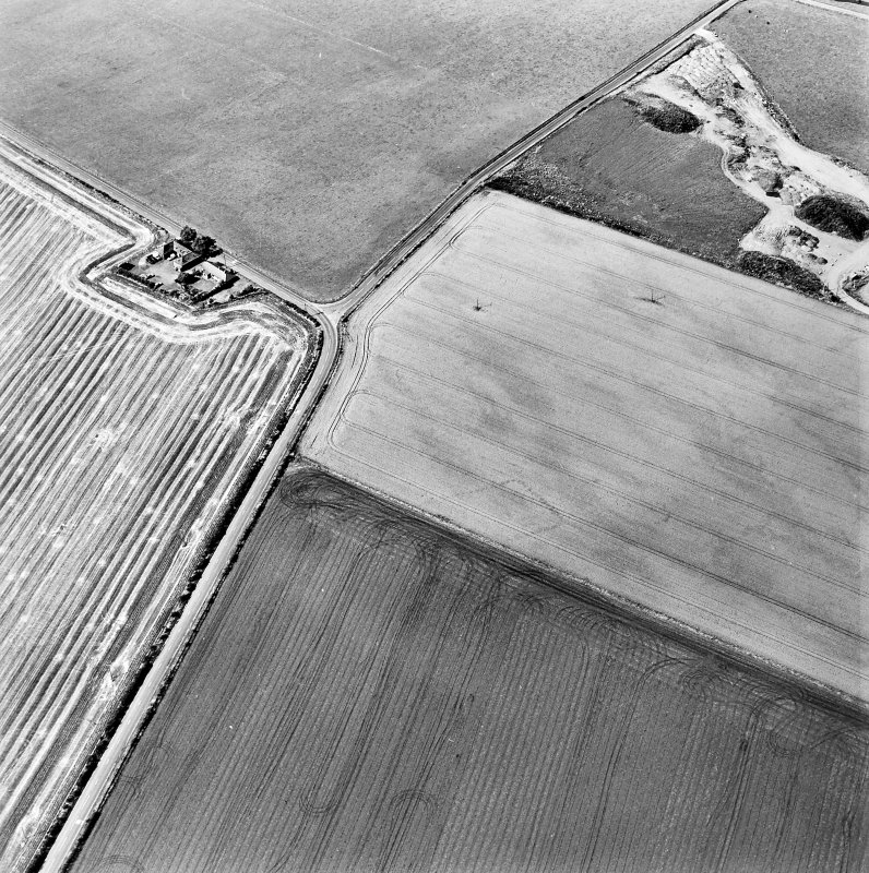 Oblique aerial view centred on the cropmarks of the NE terminal of a pit-defined cursus with ring-ditches, pits and cropmarks adjacent, taken from the SE.