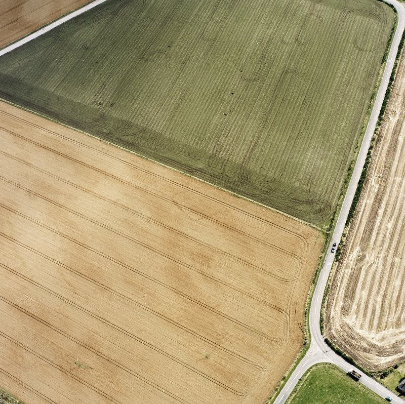 Oblique aerial views centred on the cropmarks of the NE terminal of a pit-defined cursus with ring-ditches, pits and cropmarks adjacent, taken from the NW.