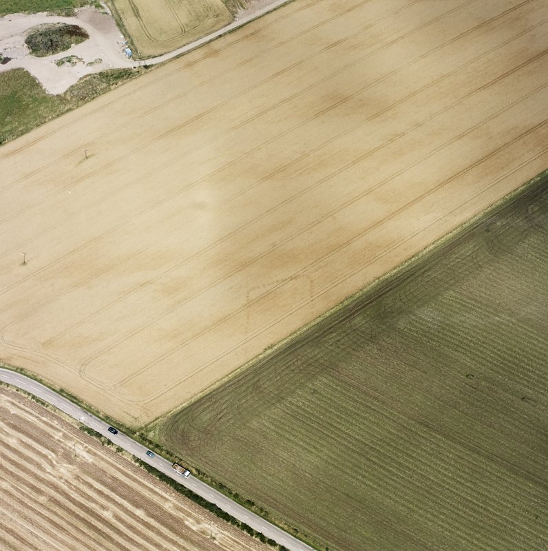 Oblique aerial views centred on the cropmarks of the NE terminal of a pit-defined cursus with ring-ditches, pits and cropmarks adjacent, taken from the SW.