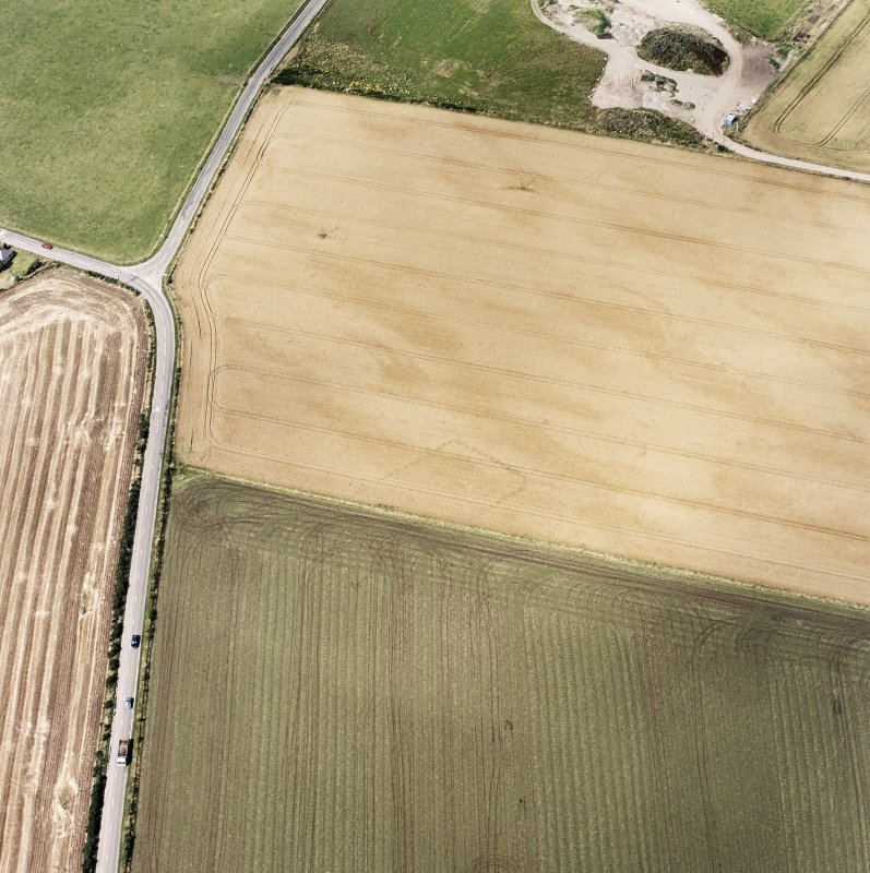 Oblique aerial views centred on the cropmarks of the NE terminal of a pit-defined cursus with ring-ditches, pits and cropmarks adjacent, taken from the SSE.
