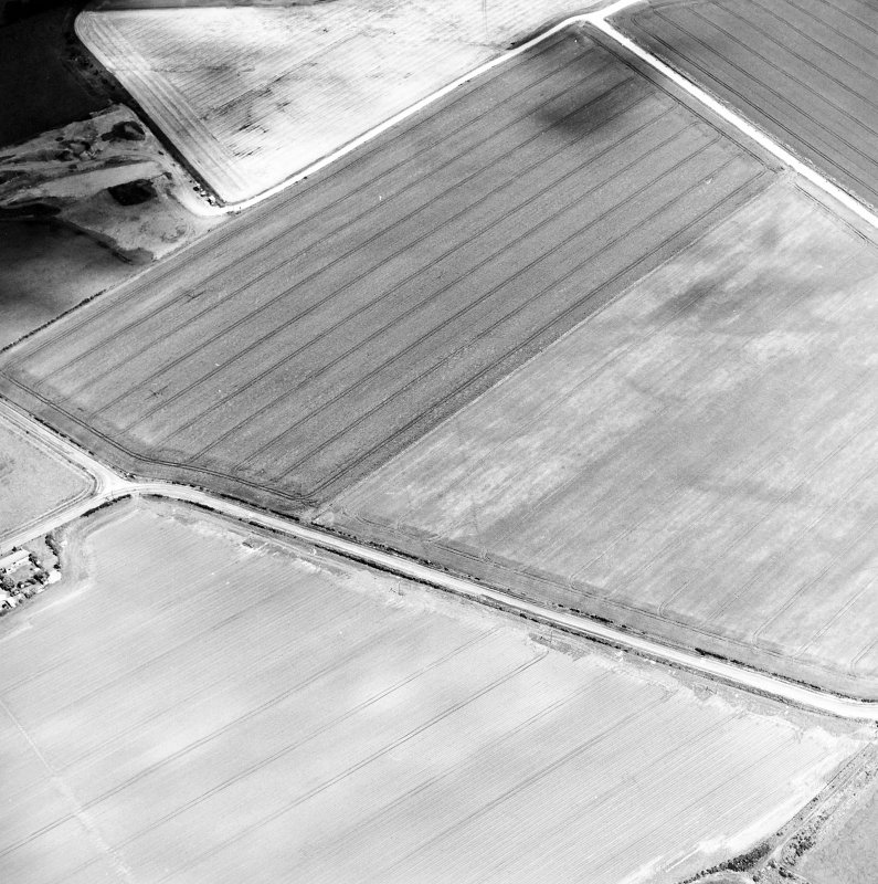 Oblique aerial view centred on the cropmarks of the pit-defined cursus with enclosure and possible barrow adjacent, taken from the SW.