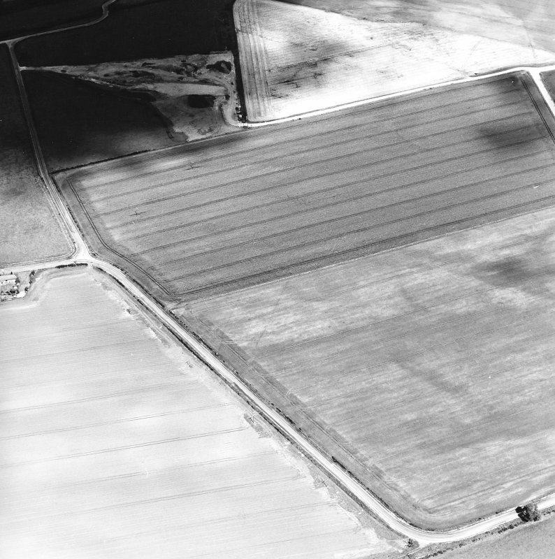 Oblique aerial view centred on the cropmarks of the pit-defined cursus with enclosure and possible barrow adjacent, taken from the SSW.