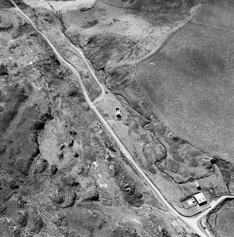 Oblique aerial photograph of Kilchiaran, Islay, taken from the E and centred on the remains of Kilchiaran chapel and burial-ground.