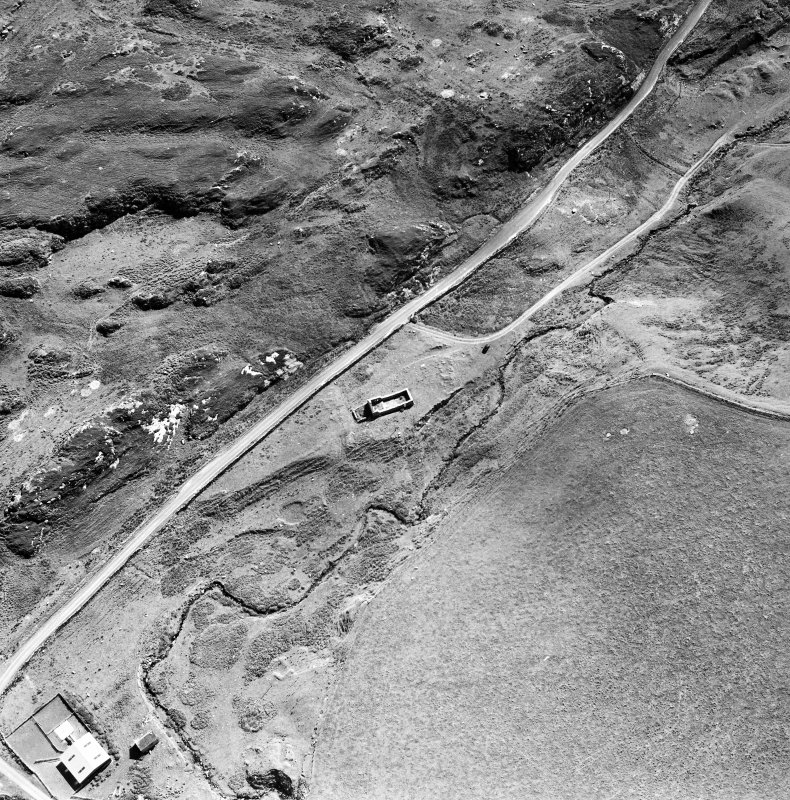 Oblique aerial photograph of Kilchiaran, Islay, taken from the NE and centred on the remains of Kilchiaran chapel and burial-ground.