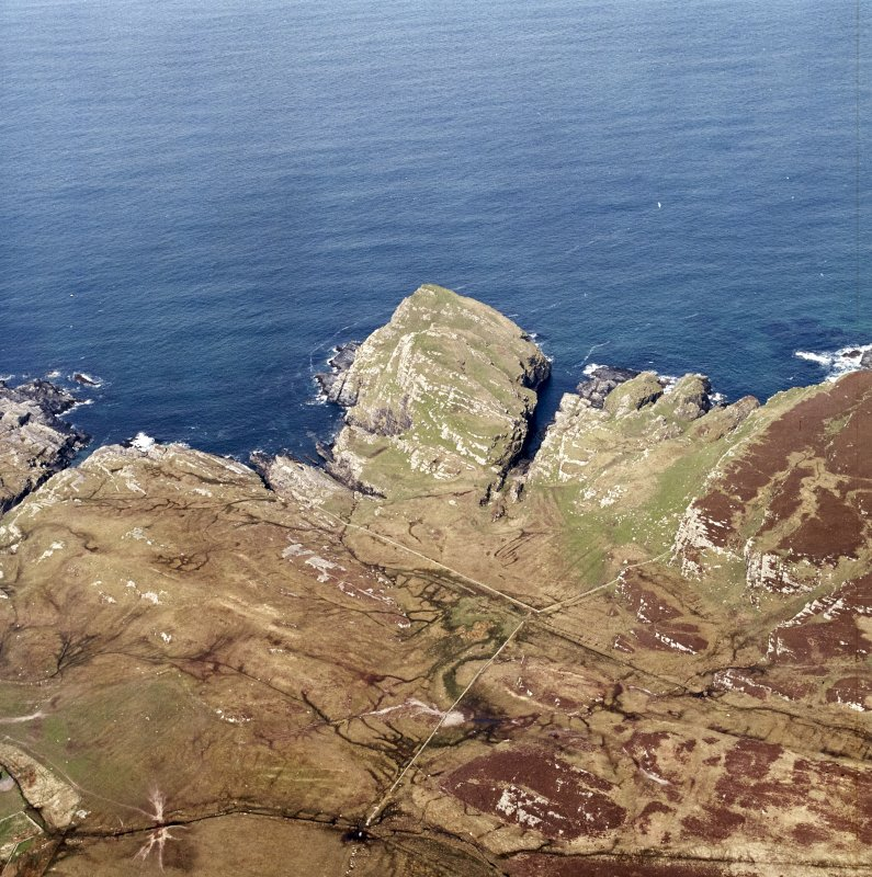Oblique aerial view centred on the remains of the fort and dun with lazy-beds adjacent, taken from the ESE.