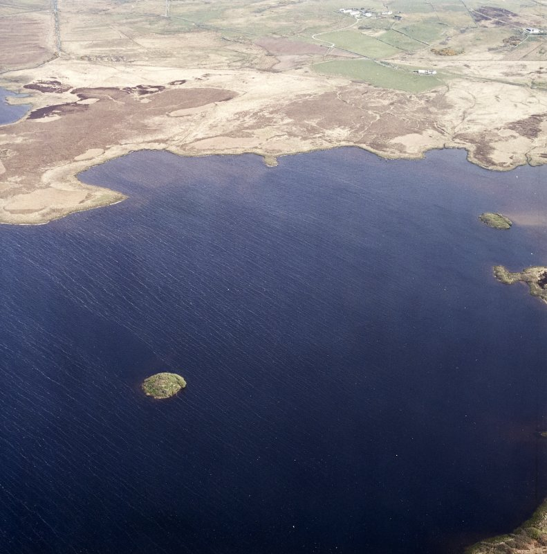 Oblique aerial view centred on the site of the castle with the remains of the possible crannog, farmstead, rig and township adjacent, taken from the SW.