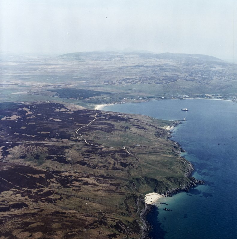 General oblique aerial view looking across the remains of the farmstead, townships and lazy-beds towards Kilnaughton Bay and the S of Islay with the Paps of Jura beyond, taken from the SW.
