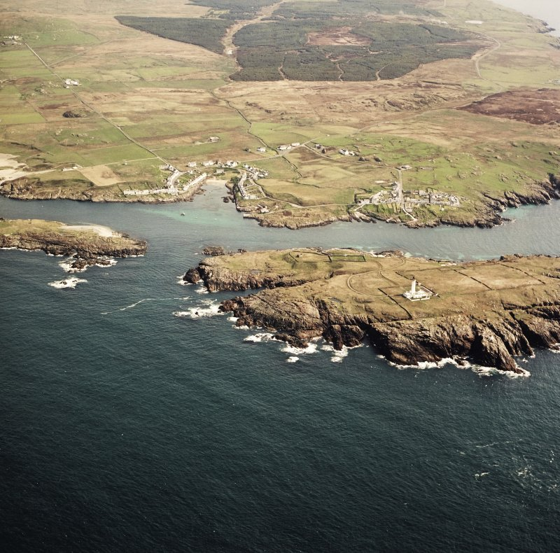 General oblique aerial view centred on the villages, lighthouse, cottage and remains of the chapel and burial ground, taken from the SW.