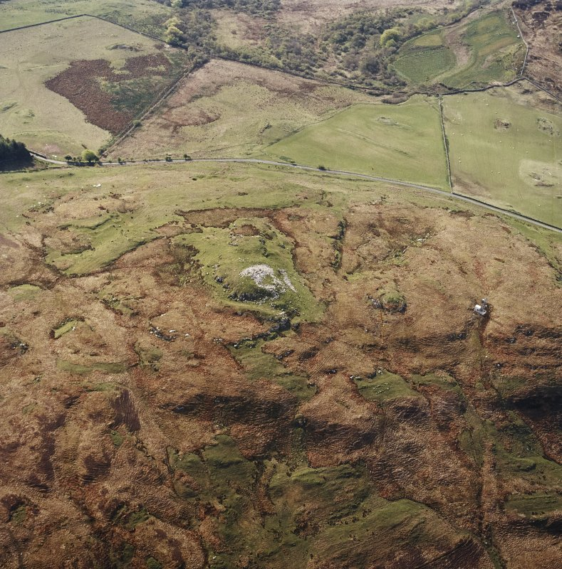 Oblique aerial view centred on the remains of the broch, taken from the NW.