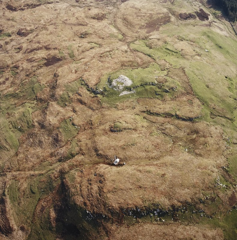 Oblique aerial view centred on the remains of the broch, taken from the WSW.