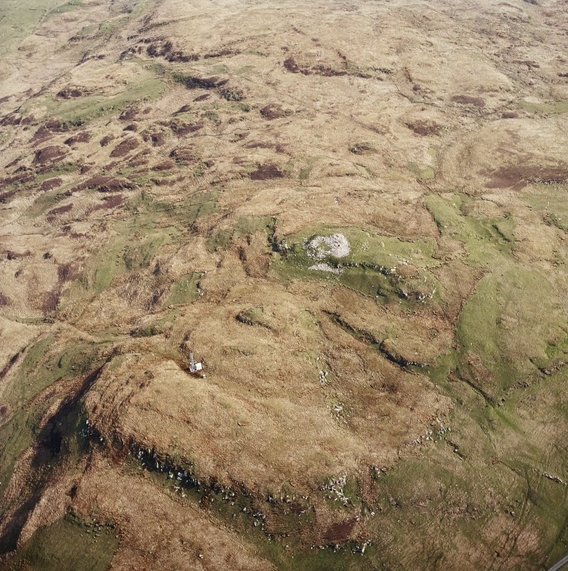 Oblique aerial view centred on the remains of the broch, taken from the SW.