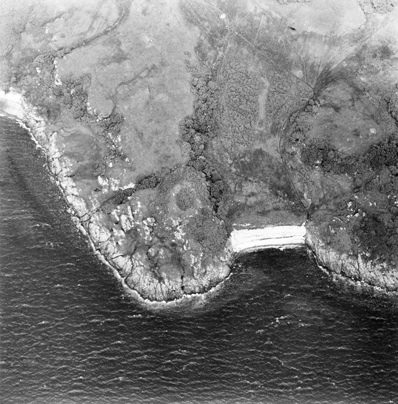 Oblique aerial view centred on the remains of the dun, taken from the SW.