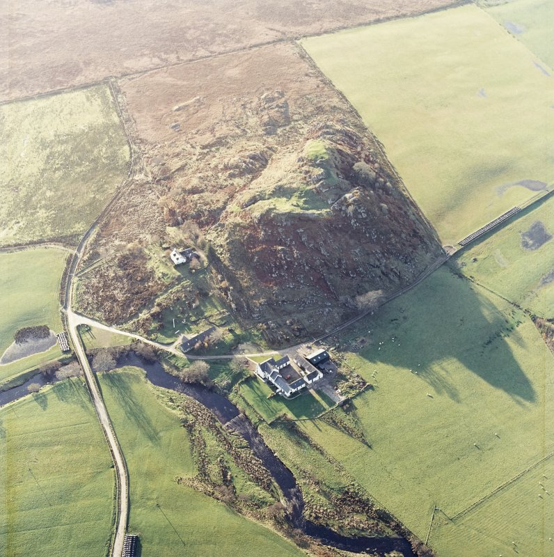 Oblique aerial view centred on the remains of the fort with the farmstead adjacent, taken from the NE.