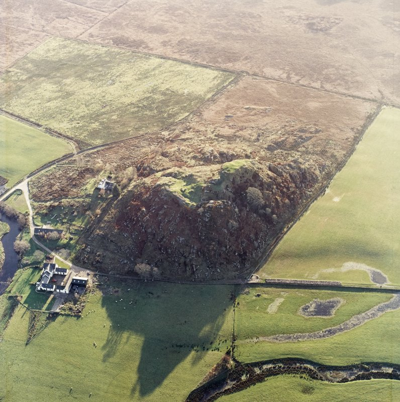 Oblique aerial view centred on the remains of the fort with the farmstead adjacent, taken from the NNE.