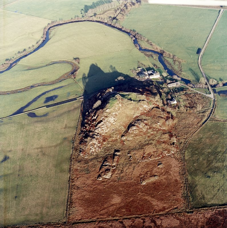 Oblique aerial view centred on the remains of the fort with the farmstead adjacent, taken from the SW.