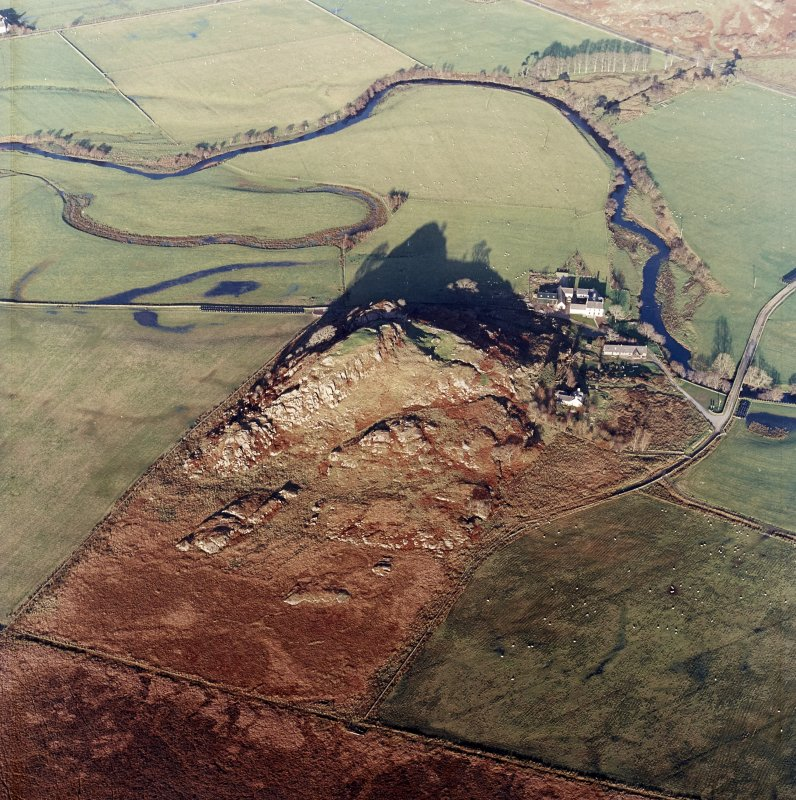 Oblique aerial view centred on the remains of the fort with the farmstead adjacent, taken from the SSW.